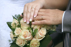 Hands of the bride and groom over wedding bouquet Stock Images