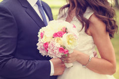 Hands of a bride and groom with peonies bouquet Stock Photography