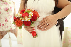 Hands of a bride and groom with red bouquet Stock Image