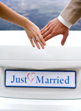 Hands of bride and groom with rings. On the background of Just Married Stock Images