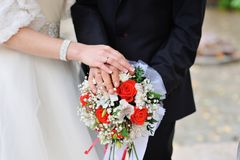 Hands of the bride and groom with rings on a beautiful bouquet Stock Images
