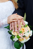 Hands of the bride and groom with rings on a beautiful wedding bouquet Stock Photos