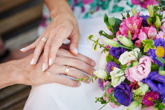 Hands of the bride and groom with rings on a beautiful wedding bouquet Royalty Free Stock Photo
