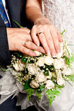 Hands of the bride and groom with rings on bouquet Stock Photos