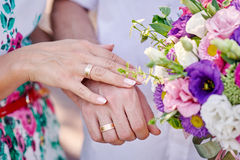 Hands of bride and groom with rings and bouquet Royalty Free Stock Photography