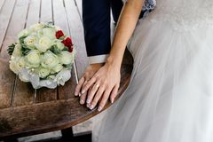 Hands of bride and groom with rings and bouquet of white roses and orchids on the table. Close up Stock Photos