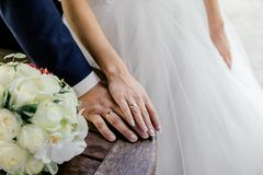 Hands of bride and groom with rings and bouquet of white roses and orchids on the table. Close up Royalty Free Stock Photo