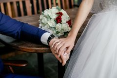 Hands of bride and groom with rings and bouquet of white roses and orchids on the table. Close up Stock Photo
