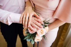 Hands of the bride and groom with rings on the bridal bouquet Royalty Free Stock Image
