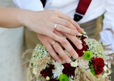 Hands of the bride and groom with rings on wedding bouquet Royalty Free Stock Images