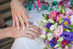 Hands of bride and groom with rings and wedding bouquet Stock Photos