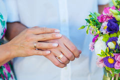 Hands of bride and groom with rings and wedding bouquet Royalty Free Stock Photography