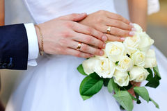 Hands of bride and groom with rings on wedding bouquet Stock Photos