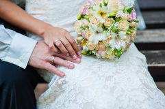 Hands of bride and groom with rings on wedding bouquet Stock Photo