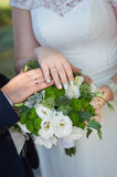 Hands of the bride and groom with rings for wedding bouquet Stock Images