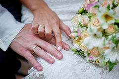 Hands of bride and groom with rings wedding bouquet Royalty Free Stock Photo
