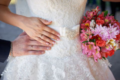 Hands of bride and groom with rings wedding bouquet Stock Images
