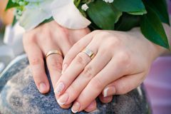 Hands of bride and groom and rings with wedding bouquet Royalty Free Stock Photography