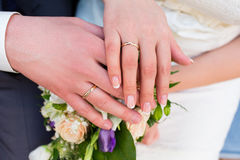 Hands of the bride and groom with rings on wedding bouquet Stock Photography