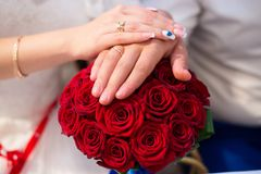Hands of bride and groom with rings on wedding bouquet. Marriage concept stock photos
