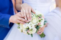 Hands of bride and groom with rings on wedding bouquet. Marriage concept stock photography