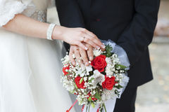 Hands of bride and groom with rings on wedding bouquet of roses Stock Photos