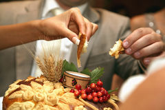Hands bride and groom salt a piece of wedding loaf Stock Photo