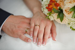 Hands of Bride and groom showing their wedding rings. On background of Bride`s bouquet Stock Photo