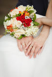 Hands of Bride and groom showing their wedding rings. On background of Bride`s bouquet Royalty Free Stock Photography