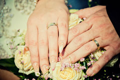 Hands of bride and groom with wedding bouquet Stock Photo