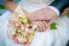 Hands of the bride and groom. Hands of the bride and groom on the wedding bouquet Stock Photography