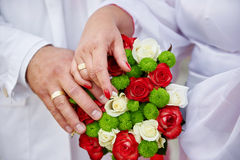 Hands of bride and groom and wedding bouquet Stock Image