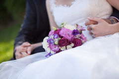 Hands of the bride and groom and wedding bouquet Royalty Free Stock Photography
