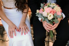 Hands of bride and groom with wedding bouquet Royalty Free Stock Photos