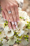 Hands of bride and groom on wedding bouquet. Marriage concept Royalty Free Stock Photography