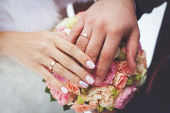 Hands of bride and groom on wedding bouquet. Marriage concept Royalty Free Stock Image