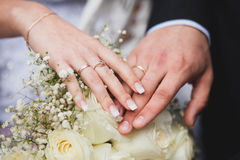 Hands of bride and groom on wedding bouquet. Marriage concept Stock Photo