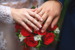Hands of bride and groom on wedding bouquet. Marriage concept Stock Photography