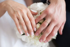 Hands of bride and groom on wedding bouquet. Marriage concept Royalty Free Stock Photo