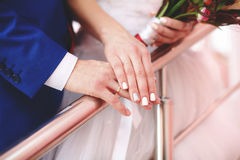 Hands of bride and groom on wedding bouquet. Marriage concept Stock Image