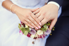 Hands of bride and groom on wedding bouquet. Marriage concept Stock Photos
