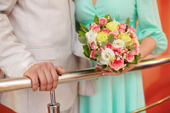 Hands of bride and groom and wedding bouquet. Marriage concept Stock Photography