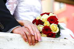 Hands of bride and groom and wedding bouquet Stock Photos