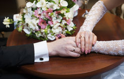 Hands of the bride and groom and wedding flowers Royalty Free Stock Photo