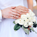 Hands of the bride and groom with wedding rings on bouquet Stock Photos
