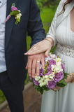 Hands of the bride and groom with wedding rings on a bouquet of Stock Images