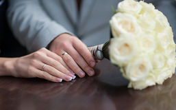 Hands of bride and groom with wedding rings and bouquet of roses Royalty Free Stock Photography