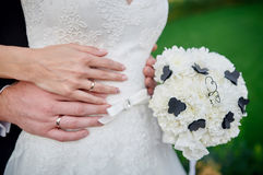 Hands bride and groom with wedding rings a bouquet of white flowers Royalty Free Stock Image