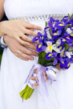 Hands of bride and groom with wedding rings and wedding bouquet of irises Royalty Free Stock Photo