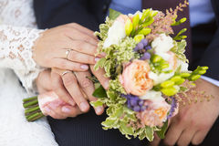 Hands of bride and groom with wedding rings and wedding bouquet. Of violet, pink and white flowers Royalty Free Stock Image